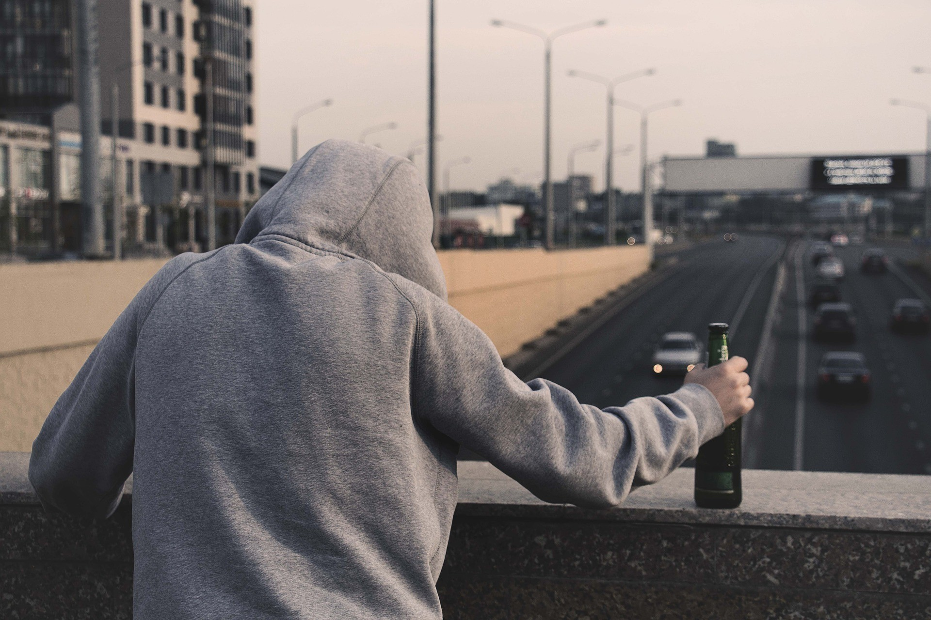 substance-abuse-hoodie-with-bottle-on-bridge